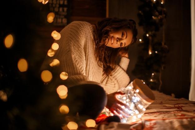 Bella ragazza in un maglione vintage lavorato a maglia con un barattolo magico con luci festive su un letto alla vigilia di natale