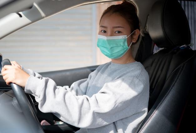 Bella ragazza in una maschera che si siede in un'automobile,