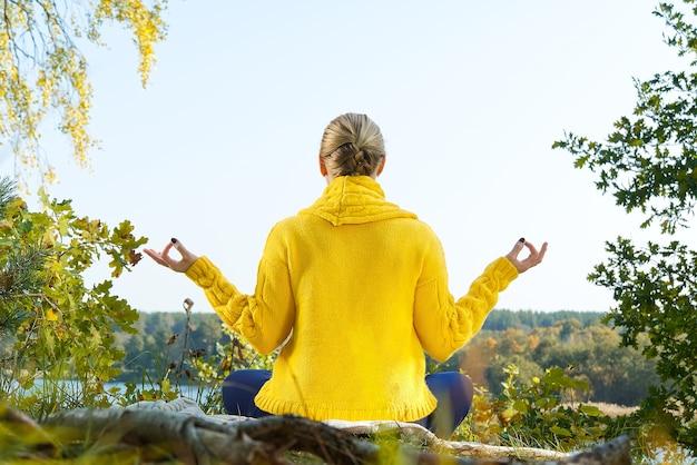 Bella ragazza che medita in autunno parco donna medita nella foresta