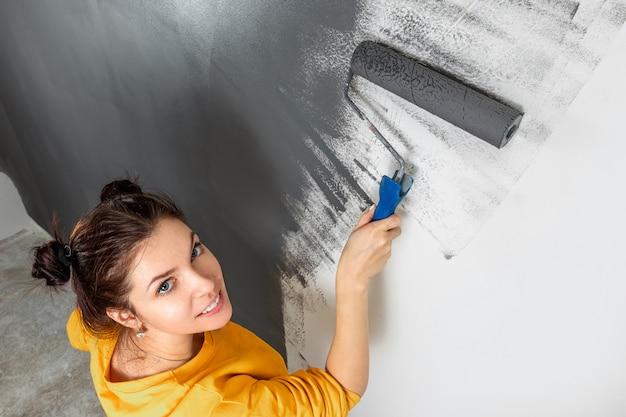 La bella ragazza dipinge una parete in una giacca gialla con un rullo, pittura grigia. il concetto di riparazione, cambiamento, design, interni.