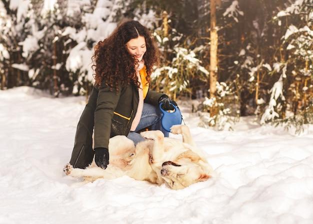 La bella ragazza gioca con l'inverno del dabrodor del cane nei boschi