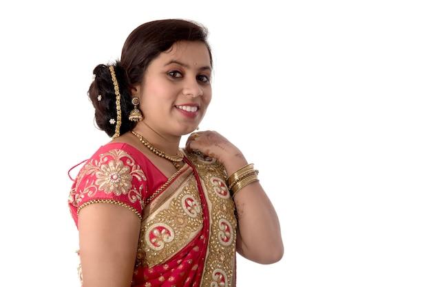 Bella ragazza che posa in saree tradizionale indiano sulla parete bianca.