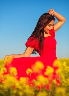 Bella ragazza in un vestito rosso che posa in un campo con la colza. donna felice sulla natura. stagione primaverile, giornata calda.