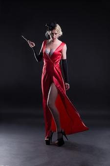Bella ragazza in un vestito rosso con una sigaretta, in stile cabaret, isolato su uno sfondo scuro.
