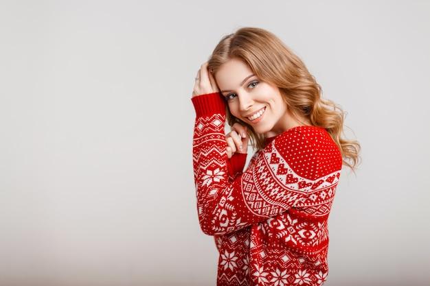 Bella ragazza in un maglione vintage rosso su sfondo grigio