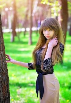 Bella ragazza che si rilassa in una foresta verde in primavera