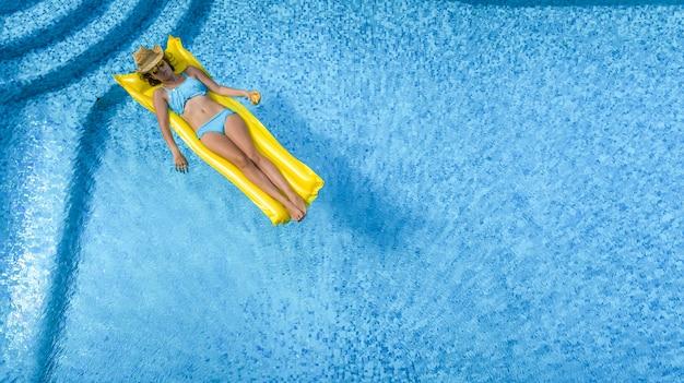 Bella ragazza che si rilassa in piscina, la donna nuota sul materasso gonfiabile e si diverte in acqua in vacanza con la famiglia, località di villeggiatura tropicale, vista aerea drone dall'alto