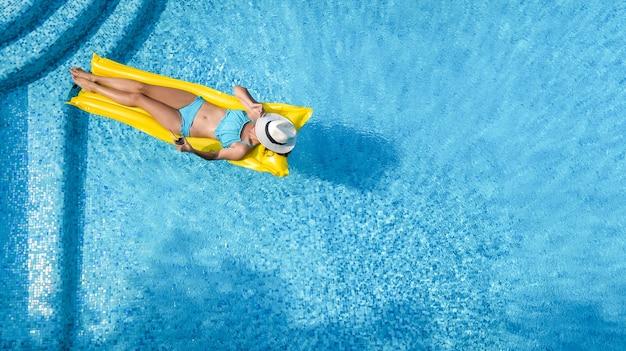 Bella ragazza che si distende in piscina, la donna nuota sul materasso gonfiabile e si diverte in acqua in vacanza con la famiglia, località di villeggiatura tropicale, vista aerea drone dall'alto
