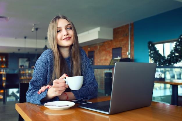 Bella ragazza che riposa in un caffè