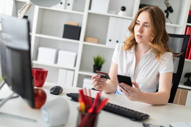 Bella ragazza si siede in ufficio, tiene una carta di credito e un telefono in mano.