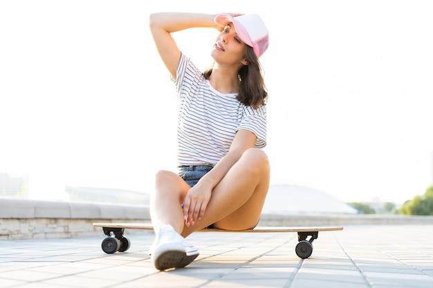 Bella ragazza che si siede sul longboard in tempo soleggiato.