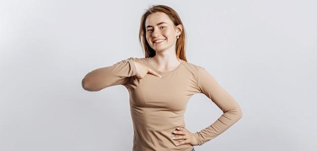 Bella ragazza che sorride e che indica il suo dito contro se stessa su uno spazio bianco isolato