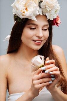 Bella ragazza sorridente e in posa con fiori sul muro grigio in abito bianco ritratto