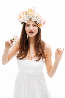 Bella ragazza sorridente e in posa con fiori sul muro bianco in abito bianco ritratto