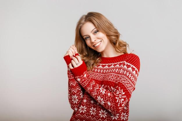 Bella ragazza sorridente in un maglione rosso con ornamento su uno sfondo grigio al chiuso