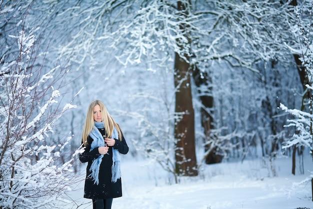 Bella ragazza sorridente e camminando per la strada. bello inverno nevoso freddo. atmosfera di vacanza.