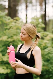 Bella ragazza in divisa sportiva con una bottiglia di acqua che fa yoga e sport nella foresta all'aria aperta