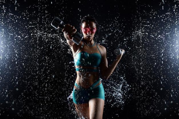La bella ragazza in abiti sportivi posa con le teste di legno nello studio dell'acqua
