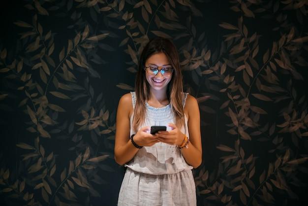 La bella ragazza che sta appoggiata si è appoggiata la parete che esamina il suo telefono cellulare sorridendo e guardando nell'amore.