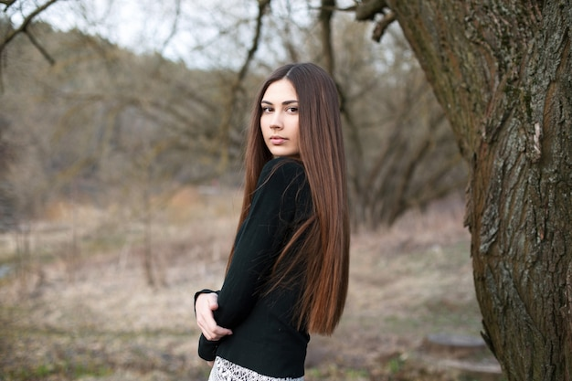 Bella ragazza in piedi vicino a un albero in giardino