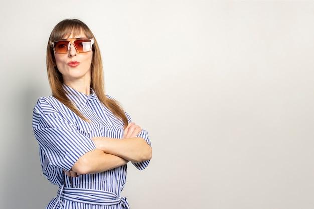 Bella ragazza in occhiali da sole su sfondo chiaro
