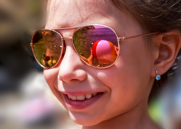Bella ragazza in occhiali da sole con la riflessione del pallone da spiaggia