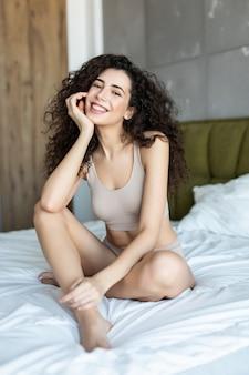 Bella ragazza in biancheria intima a letto a casa