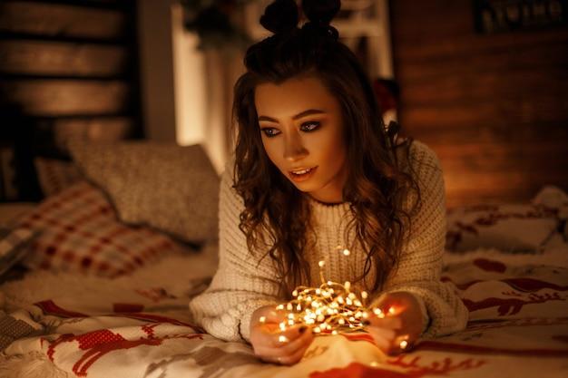 Bella ragazza in maglione lavorato a maglia vintage con luci festive che riposa sul letto a natale