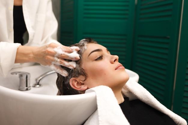 La bella ragazza si lava la testa in una bellezza. il parrucchiere sta lavando i capelli per il cliente