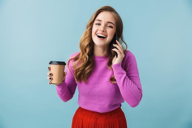 Bella ragazza che indossa abiti casual in piedi isolata sul muro blu, bevendo caffè mentre parla al cellulare
