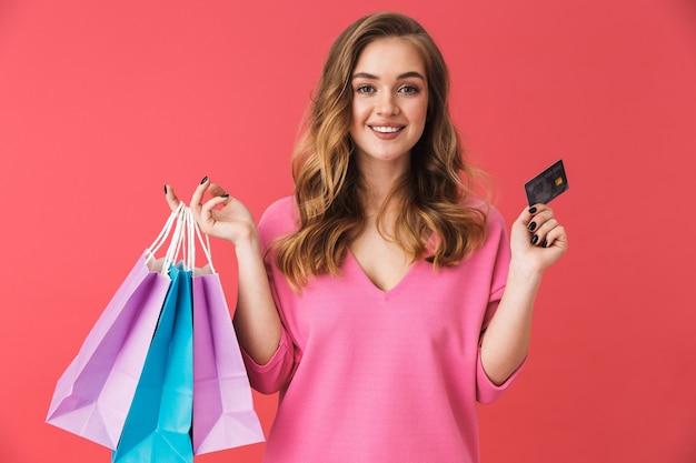 Bella ragazza che indossa abiti casual in piedi isolata sul muro rosa, portando borse della spesa, mostrando carta di credito