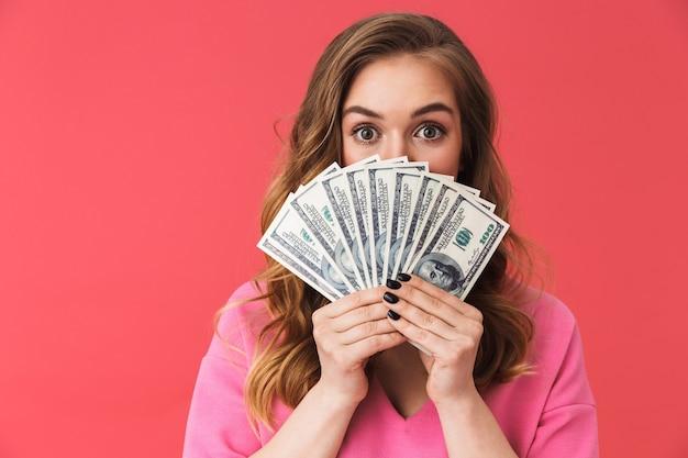 Bella ragazza che indossa abiti casual in piedi isolata sul muro rosa, mostrando banconote in denaro