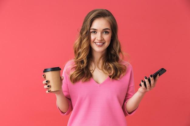 Bella ragazza che indossa abiti casual in piedi isolata sul muro rosa, usando il telefono cellulare mentre beve caffè da asporto