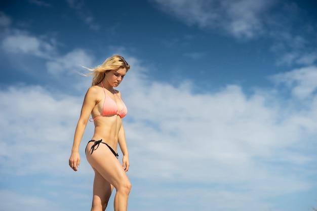 Bella ragazza che indossa il costume da bagno sullo sfondo del cielo. giorno d'estate e concetto di vacanza felice.