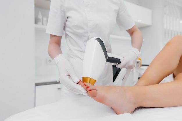 Una bella ragazza eseguirà una procedura di epilazione laser con moderne attrezzature nel primo piano del salone della stazione termale