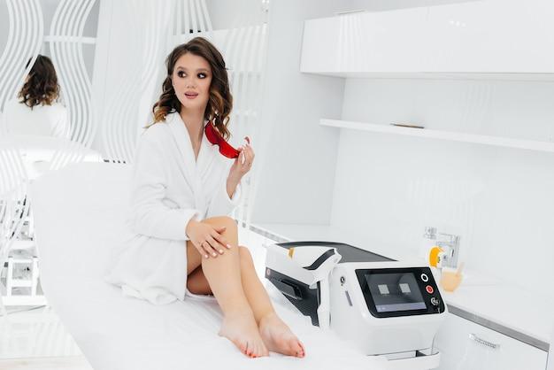 Una bella ragazza verrà sottoposta a depilazione laser con moderne attrezzature in un salone spa. salone di bellezza. cura del corpo.