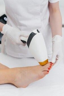 Una bella ragazza verrà sottoposta a depilazione laser con moderne attrezzature in un salone spa
