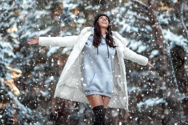 Bella ragazza nella foresta di inverno, la neve sta cadendo