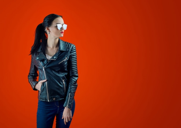 Bella ragazza con i capelli neri in una giacca di pelle e occhiali da sole alla moda su un muro rosso brillante.