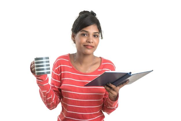 Bella ragazza con il libro e la tazza di caffè in posa su un muro bianco.
