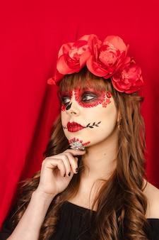 Bella ragazza con il trucco dia de los muertos che guarda a sinistra con sfondo rosso.
