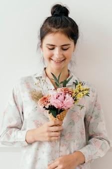 Bella ragazza con fiori in un cono gelato