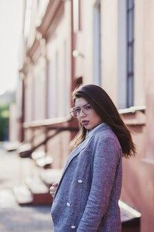 Bella ragazza con gli occhiali in una giacca in giro per la città