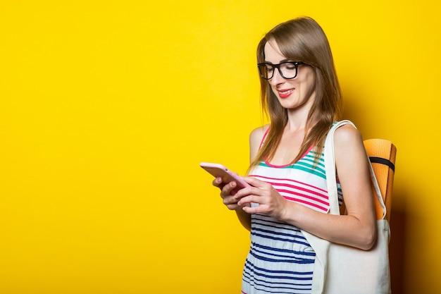 Bella ragazza giovane con karimat in una borsa sorridente guarda il telefono su uno sfondo giallo.