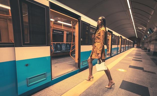 Bella ragazza giovane con belle gambe lunghe in un cappotto primaverile giallo e una borsetta bianca in metropolitana