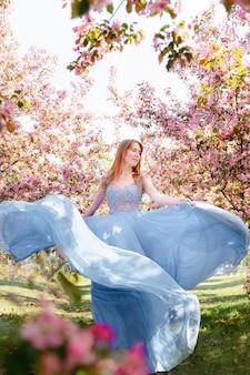 Bella ragazza con lunghi capelli rossi in un abito da ballo blu in un meleto in fiore il concetto di fioritura primaverile e femminilità