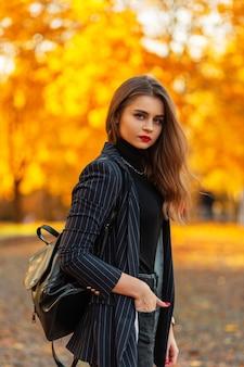 Bella ragazza con le labbra rosse in un blazer alla moda con un maglione nero, catena e zaino cammina nella natura con fogliame autunnale dorato al tramonto