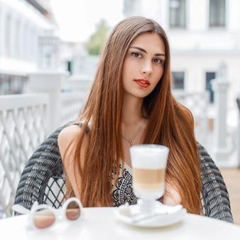 Bella ragazza con le labbra rosse riposa in un caffè in una giornata di sole.