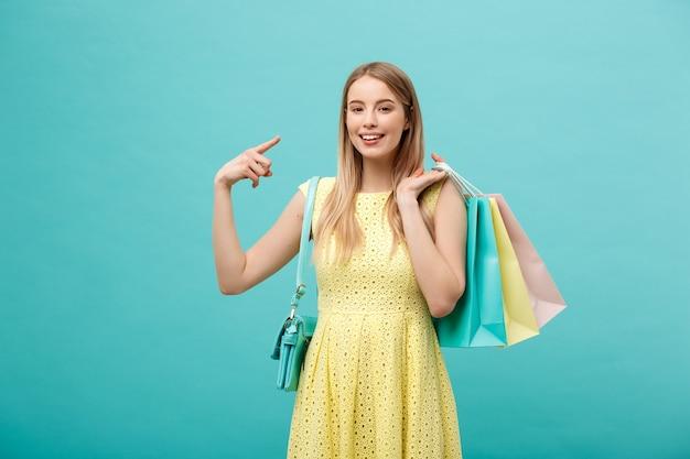 La bella ragazza con la borsa della spesa in abito giallo indica qualcosa con il dito.