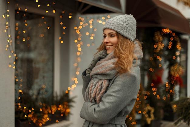 Bella ragazza con un dolce sorriso in un cappotto invernale grigio alla moda in un cappello lavorato a maglia con una sciarpa vicino alle luci della città